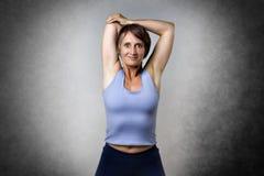 Donna invecchiata mezzo che fa allungamento Fotografia Stock Libera da Diritti
