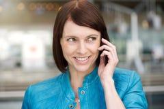 Donna invecchiata mezzo che per mezzo del telefono cellulare Immagine Stock