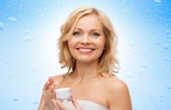 Donna invecchiata mezzo felice con crema d'idratazione Immagini Stock