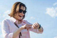 Donna invecchiata mezzo felice di affari che esamina orologio Donna in vetri, cielo blu del fondo in nuvole fotografia stock