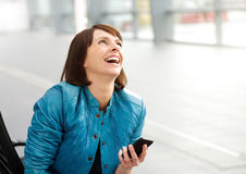 Donna invecchiata mezzo sorridente con il telefono cellulare Fotografia Stock Libera da Diritti