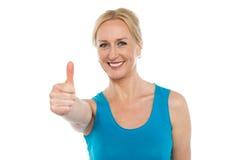 Donna invecchiata sorridente che mostra i pollici in su Immagini Stock