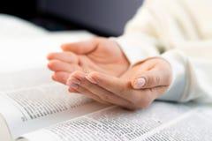 Donna irriconoscibile che legge grande libro - bibbia santa e pregare Scripture di studio cristiano Studente nell'istituto univer immagini stock