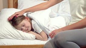 Donna irriconoscibile che pieghetta la coperta per la sua piccola figlia addormentata stock footage