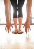 Donna irriconoscibile che si esercita a casa, allungando le gambe e braccio Fotografie Stock