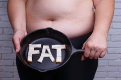 Donna irriconoscibile di peso eccessivo che tiene una pentola con l'automobile del grasso di parola immagini stock libere da diritti