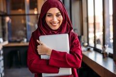 Donna islamica allegra nel hijab con il computer portatile al caffè immagini stock