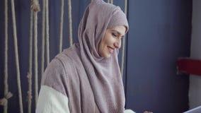 Donna islamica che passa in rassegna sul computer portatile in caffè stock footage