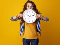 Donna isolata su fondo giallo che si nasconde dietro l'orologio Immagine Stock Libera da Diritti