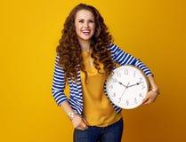 Donna isolata su giallo con l'orologio che esamina lo spazio della copia Immagine Stock Libera da Diritti