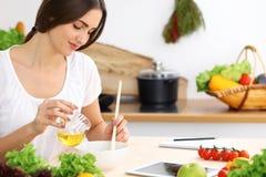 Donna ispana bella che cucina nella cucina mentre per mezzo del computer della compressa e del cucchiaio di legno Nuova ricetta t immagini stock