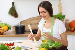 Donna ispana bella che cucina nella cucina mentre per mezzo del computer della compressa e del cucchiaio di legno Nuova ricetta t fotografia stock