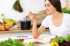 Donna ispana bella che cucina nella cucina mentre per mezzo del computer della compressa e del cucchiaio di legno Nuova ricetta t fotografie stock