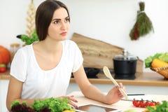 Donna ispana bella che cucina nella cucina mentre per mezzo del computer della compressa e del cucchiaio di legno Nuova ricetta t fotografia stock libera da diritti