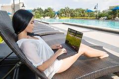 Donna ispana che ottiene abbronzatura del poolside Fotografia Stock Libera da Diritti