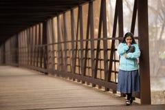 Donna ispana che prega e che tiene bibbia su un ponte fotografia stock