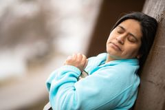 Donna ispana che si appoggia pregare della parete fotografia stock libera da diritti
