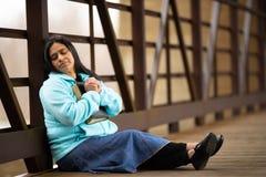 Donna ispana che si siede su un ponte che prega mentre tenendo bibbia fotografia stock
