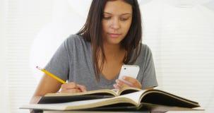 Donna ispana che studia e che per mezzo dello smartphone sullo scrittorio Fotografie Stock