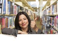Donna ispana con i pollici su sul bordo bianco in biblioteca Immagini Stock