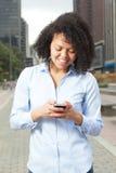 Donna ispana nel messaggio di scrittura della città con il telefono Fotografie Stock Libere da Diritti