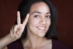 Donna ispanica abbastanza giovane che fa il segno di pace Fotografia Stock