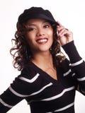 Donna ispanica abbastanza giovane con la mano al cappello Fotografia Stock