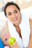 Donna ispanica atletica con un tovagliolo e una mela Fotografia Stock