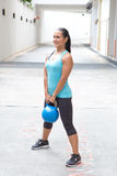 Donna ispanica sportiva in blu che solleva kettlebell blu per ascensore morto, all'aperto Immagini Stock