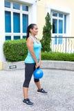 donna ispanica sportiva nell'addestramento blu con il kettlebell che fa ascensore morto Fotografia Stock Libera da Diritti