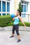 Donna ispanica sportiva nell'addestramento blu con il kettlebell che fa la routine pulita Immagini Stock Libere da Diritti