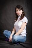 Donna in jeans che si siedono sul pavimento Immagini Stock