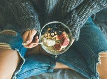 Donna in jeans e maglione miseri che mangia prima colazione sana Fotografia Stock Libera da Diritti