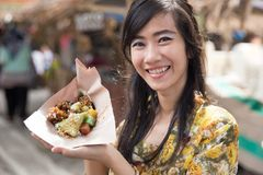 Donna in kebaya che mostra alimento tradizionale fotografia stock libera da diritti