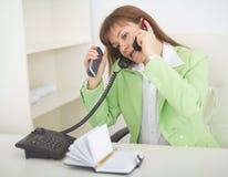 Donna - la segretaria parla da parecchi telefoni s fotografie stock