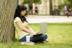 Donna latina attraente che lavora e che studing sul suo latop in un parco verde Fotografia Stock Libera da Diritti