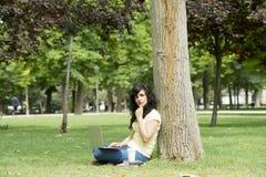 Donna latina attraente che lavora e che studing sul suo latop in un parco verde Fotografie Stock
