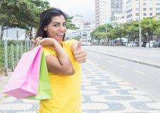 Donna latina con la camicia gialla che mostra pollice dopo la compera nella città Fotografia Stock