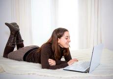 Donna latina dei capelli marroni felici che lavora al suo computer Immagine Stock