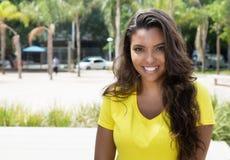 Donna latina di risata in camicia gialla che esamina macchina fotografica immagini stock libere da diritti