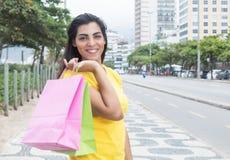Donna latina di risata con la camicia gialla dopo la compera nella città Fotografia Stock