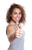 Donna latina di risata in una camicia grigia che mostra pollice su Fotografie Stock