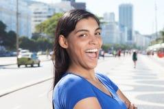 Donna latina divertente con capelli scuri lunghi nella città fotografia stock