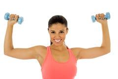 Donna latina felice attraente che tiene la testa di legno del peso che fa allenamento di forma fisica Immagine Stock Libera da Diritti