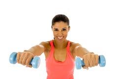 Donna latina felice attraente che tiene la testa di legno del peso che fa allenamento di forma fisica Fotografia Stock