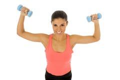 Donna latina felice attraente che tiene la testa di legno del peso che fa allenamento di forma fisica Immagini Stock