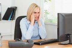 Donna lavoratrice frustrata davanti ad uno schermo Fotografie Stock Libere da Diritti