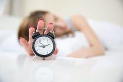 Donna a letto che estende mano fino la sveglia Immagine Stock