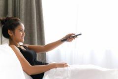 Donna a letto che guarda televisione e che giudica TV a distanza immagine stock libera da diritti