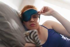 Donna a letto che sveglia il telefono cellulare sonnecchiante della sveglia fotografia stock